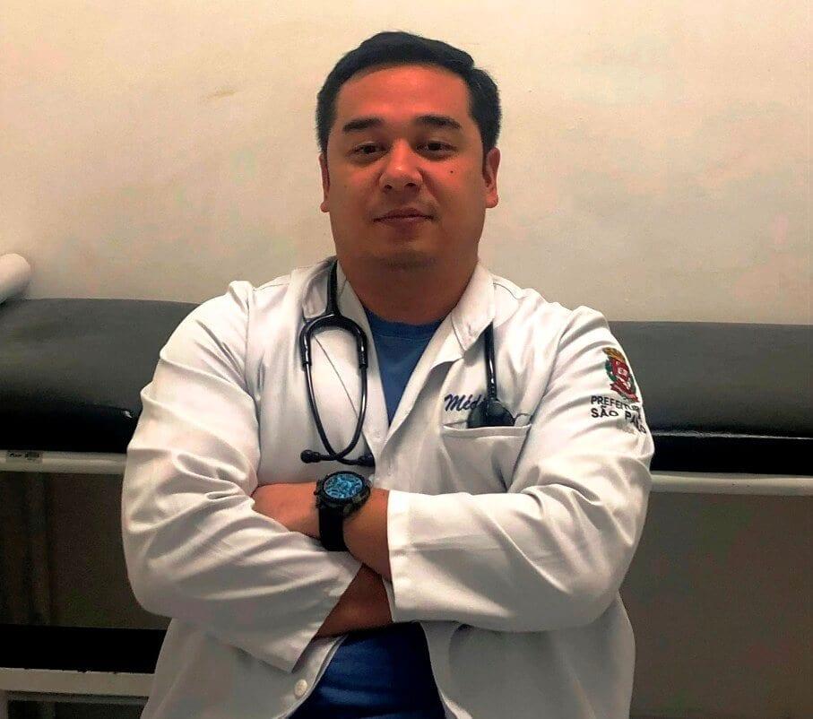 O médico do trabalho está de jaleco, de braços cruzados e está com um estetoscópio pendurado no pescoço