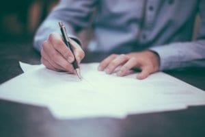 profissional escrevendo em um papel vários papeis na mesa